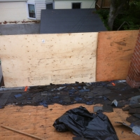 Erecting a barrier on a steep roof so old shingles do not fall onto property